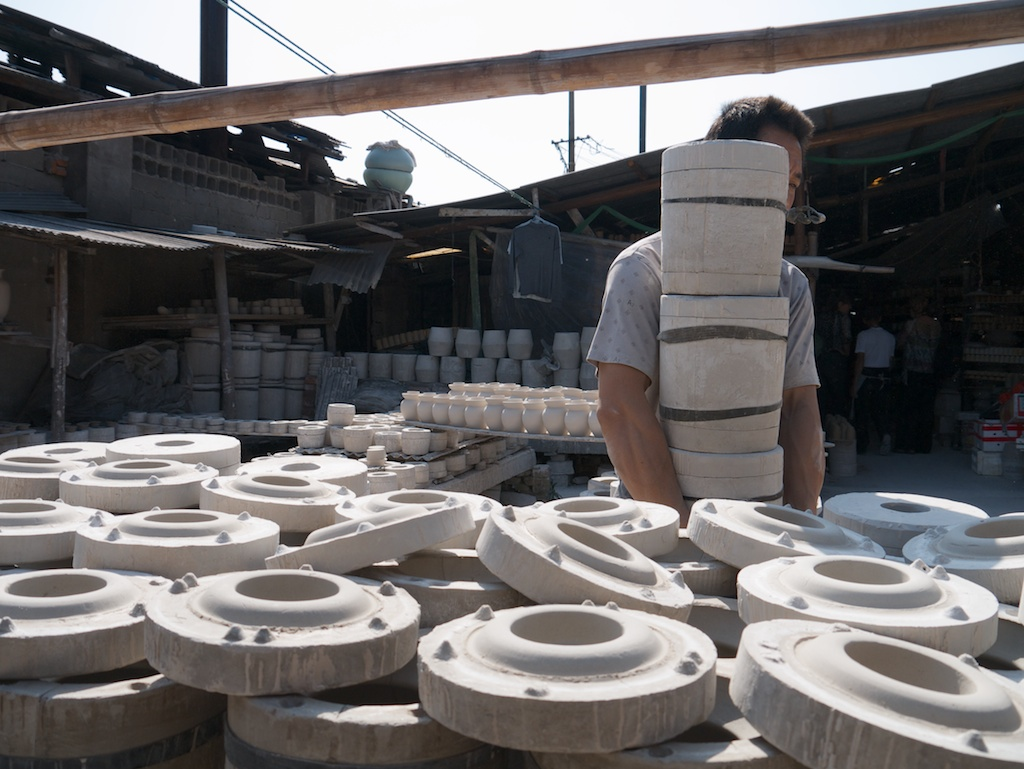 A slip-caster carries plaster moulds in a greenware factory, Jingdezhen