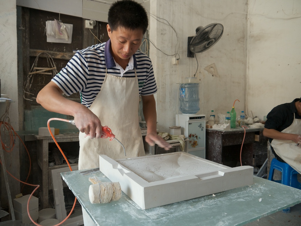 Master Tang cleans a plaster mould with compressed air in the Sculpture Factory, Jingdezhen